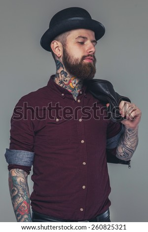 Male with tattoos in red shirt and a hat