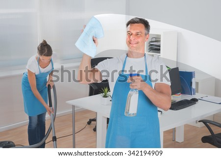 Male Worker Cleaning Glass With Rag While Female Worker Vacuuming Floor