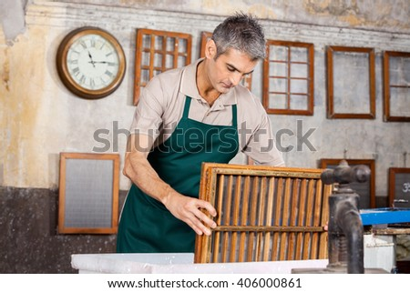 Male Worker Dipping Mold In Pulp And Water - stock photo