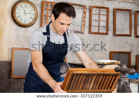 Male worker dipping mold in pulp and water at paper factory - stock photo