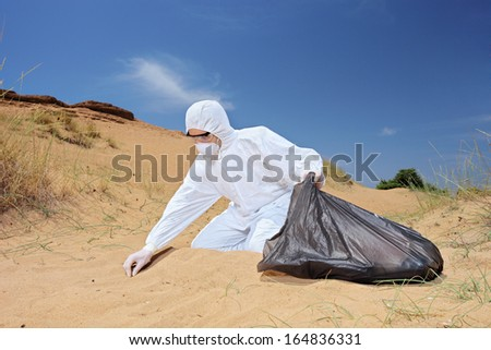 Male worker in protective suit holding a waste bag and collecting samples from sand, symbolizing pollution - stock photo
