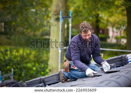 Male worker laying tiles on the roof while roofing a house near the city of Breda, Netherlands, Europe, in a traditional craftsman way - stock photo