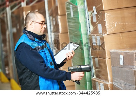 Male worker scanning package with barcode scanner in modern warehouse - stock photo