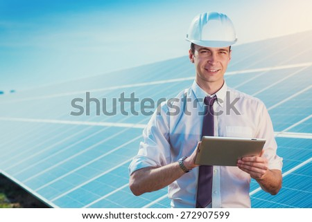 Male worker solar power plant with a tablet on a background of photovoltaic panels. - stock photo