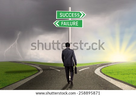 Male worker walking on the road and find two signpost with two choices to success or failure - stock photo