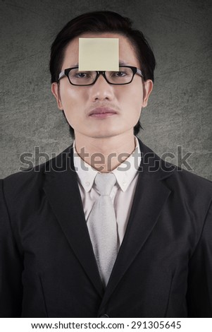 Male worker wearing business suit and attach a blank paper note on his forehead - stock photo