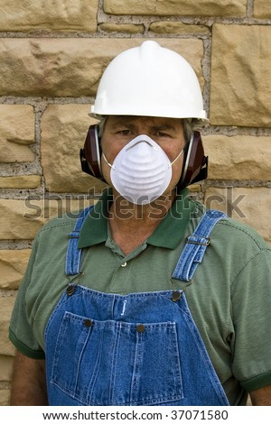 male worker wearing hardhat,ear protection,and dust mask - stock photo