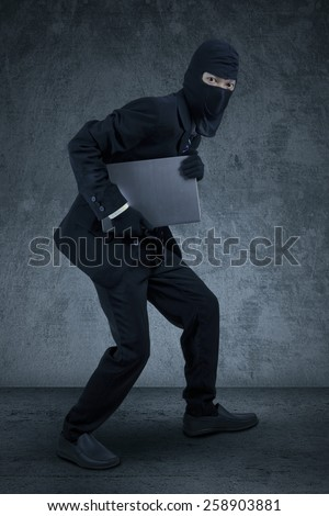 Male worker wearing mask sneaking to steal a laptop computer - stock photo