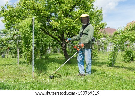 Male worker with power tool string lawn trimmer mower cutting grass. Health and safety concept. - stock photo