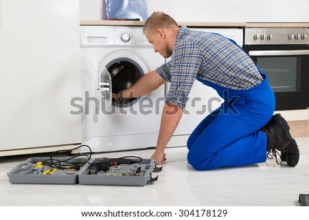Male Worker With Toolbox Repairing Washing Machine In Kitchen - stock photo