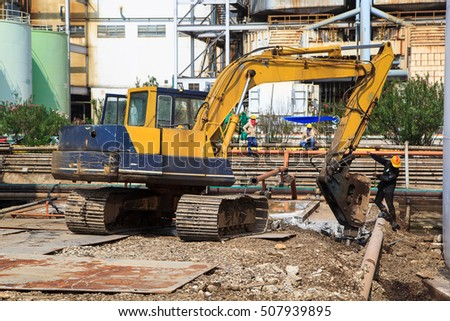 Male worker yellow excavator against construction site or demolition may be dangerous