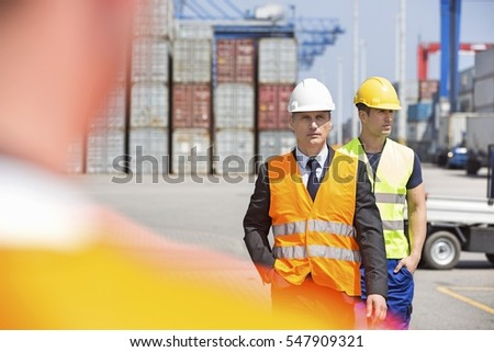 Male workers walking in shipping yard