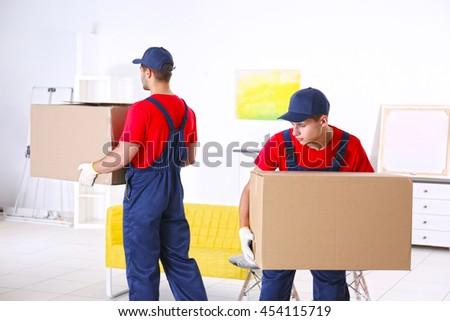 Male workers with boxes and furniture in new house - stock photo