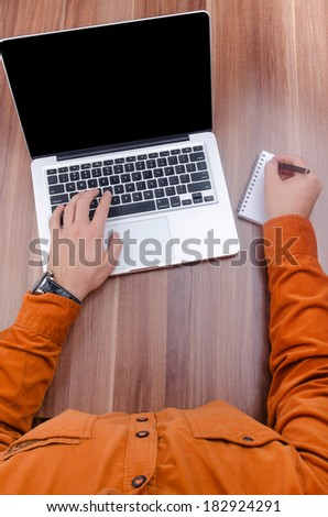 Male, working on his laptop in the office. Shot from above. - stock photo