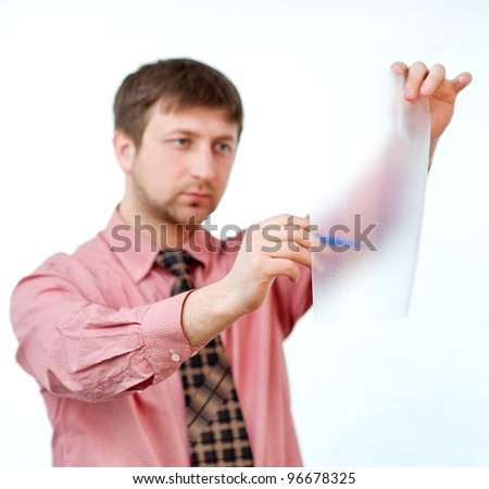 male writing something on transparent paper with marker