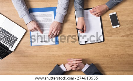 Male young candidate having a job interview with a female examiner at his side, hands top view, unrecognizable people - stock photo