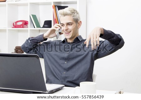 male young speaking by phone phone in the office or in the home
