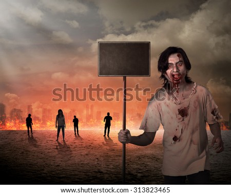 Male zombie holding wooden board over city on fire. You can put your message on the board - stock photo