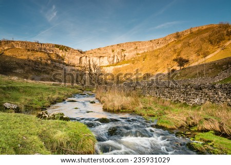 Malham Beck flows from Malham Cove / Malham Cove in Malhamdale is a popular tourist attraction of the Yorkshire Dales National Park - stock photo