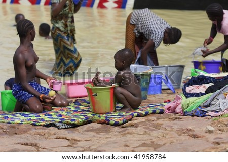 MALI - AUGUST 16: Women washing in the Niger River, the riverbank is used for cleaning utensils and clothes both as people and food, August 16, 2009 in Mopti, Mali - stock photo