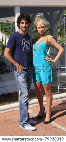 MALIBU, CA - AUG 19: Adrian Grenier takes a break from filming his documentary with Paris Hilton and poses with her at her beach house in Malibu, California on August 19, 2007
