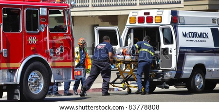 MALIBU, CALIFORNIA/USA - AUGUST 27, 2011: Unidentified firefighters help the victim of car accident on Pacific Coast Highway on August 27, 2011 in Malibu, California - stock photo