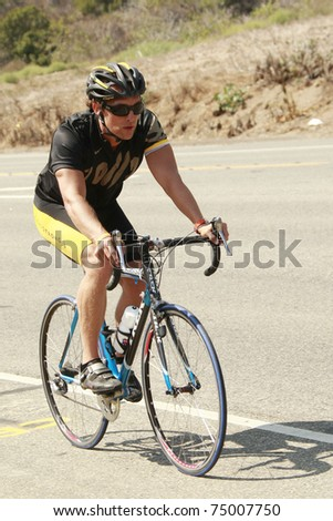 MALIBU - SEPT 11:  Matthew McConaughey trains for the triathlon along the beach by running and cycling in Malibu, California on September 11, 2008.
