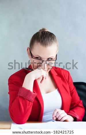 Maliciously young woman peeking behind a desk. - stock photo