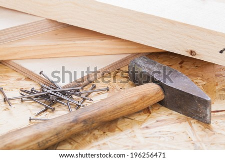 Mallet with nails and planks of new wood of varying thicknesses in a carpentry, joinery , DIY and building concept