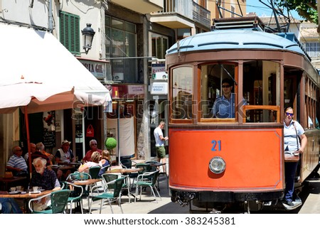 MALLORCA, SPAIN - JUNE 2: The tram is on street of Soller town and tourists are in outdoor restaurant on June 2, 2015 in Mallorca, Spain. Up to 60 mln tourists is expected to visit Spain in year 2015. - stock photo