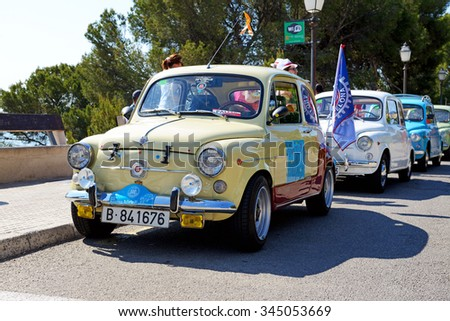 MALLORCA, SPAIN - MAY 30: The SEAT 600 classic car parade and tourists on May 30, 2015 in Mallorca, Spain. Up to 60 mln tourists is expected to visit Spain in year 2015. - stock photo