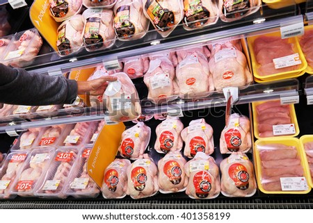 MALMEDY, BELGIUM - JULY 27, 2015: Shopper selecting packaged meat in refrigerated section of a Carrefour Hypermarket, a French multinational retailer, and large hypermarket chain.