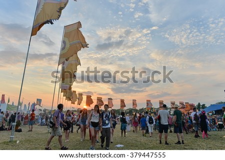 MALMESBURY, UK - JUL 26, 2014: Revellers gather at a Womad festival as the sun sets.  - stock photo