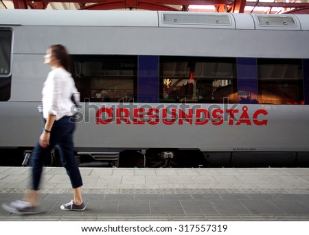MALMO, SWEDEN - FRIDAY, AUGUST 21, 2015: A pedestrian walks past a Oresundstag train at the main station in Malmo, Sweden. The train links Malmo with nearby Copenhagen, Denmark.  - stock photo