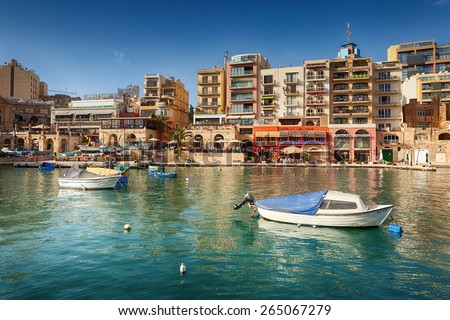 MALTA - MARCH 22 2015: Spinola Bay with boats in front of famous touristic restaurants and Portomaso tower at back at St Julian, Malta