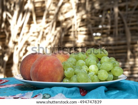 Maltese peaches and grapes prepared on a table in natural blurry background, maltese fruits. Fresh fruits peaches and grapes on a table. Fruits cocktail