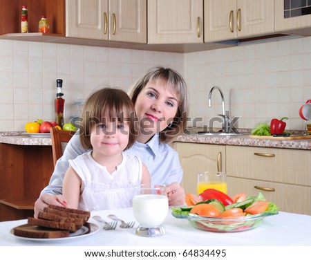 Mama and her little daughter eating breakfast in the morning together in the kitchen. - stock photo