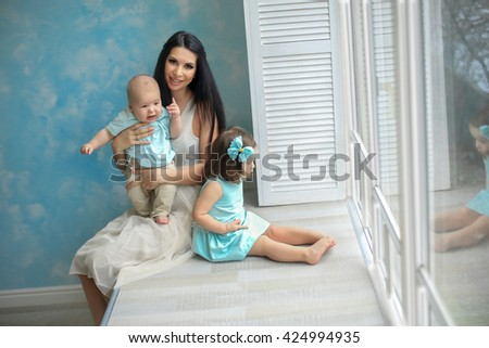 Mama brown hair in a light dress sits on a windowsill with a baby in beige pants and a shirt in his arms, and near my daughter in a blue dress and accessories is looking out the window at the head - stock photo