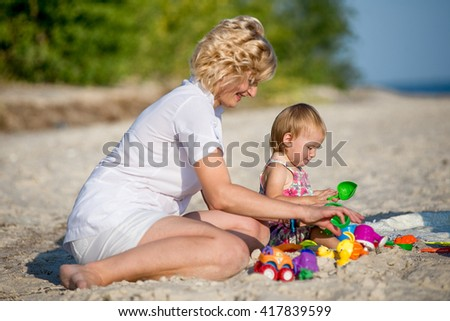 Mama with a small daughter playing on the beach in summer