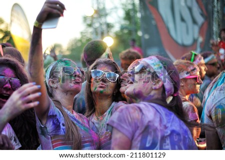 MAMAIA, ROMANIA - JULY 26: Runners take a selfie at The Color Run on July 26, 2014 in Mamaia, Romania. The Color Run is a worldwide hosted fun race with about 1500 competitors in Mamaia. - stock photo
