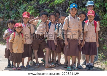 Mamasa, Sulawesi, Indonesia - August 16, 2014: Group of school children of Toraja ethnicity in brown uniform smiling while looking at the camera in the countryside of Mamasa, West Tana Toraja. - stock photo