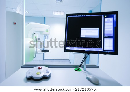 Mammography breast screening device in hospital laboratory with computer display in foreground. - stock photo