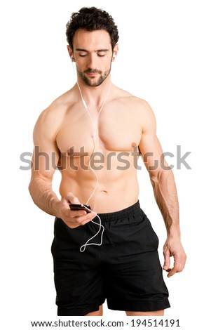 Man about to go jogging, choosing the music to hear on his mp3 player, isolated - stock photo
