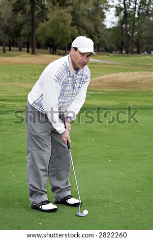 Man about to putt a golf ball - looking at the camera. - stock photo