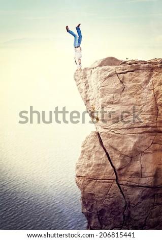 man acrobat on dangerous cliff - stock photo