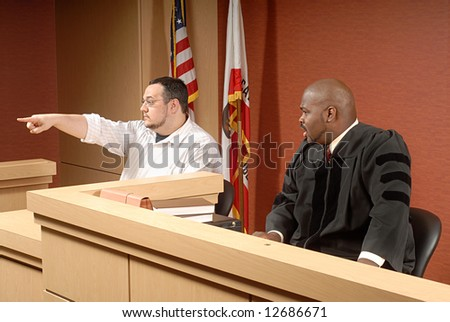 Man acting as a witness pointing out someone to the judge - stock photo