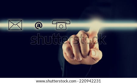 Man activating a bar with contact icons depicting the web, mail, email and telephone on a virtual screen or interface for online support and service, dark background with copyspace. - stock photo