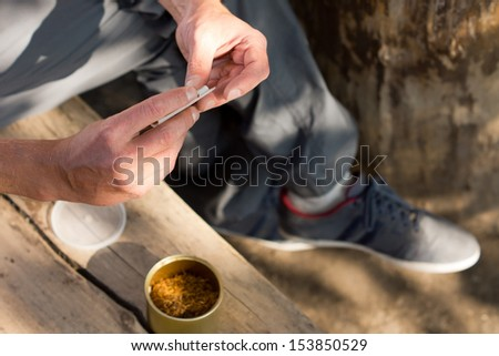 Man addicted to marijuana or cannabis rolling himself a joint sitting outdoors in the shade, close up view of the hands - stock photo