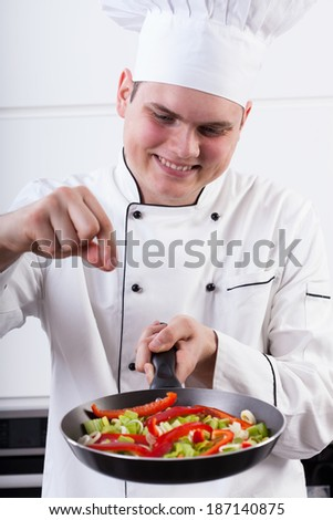 Man adding spices into vegetables in a pan