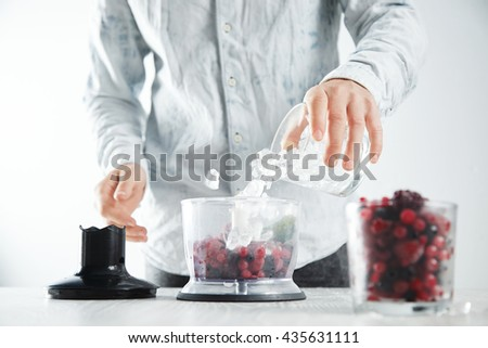 Man adds some ice cubes to blender pot with frozen berries, yougur, mint and honey before making make tasty smoothie drink to refresh in summer time. Unfocused glass with frozen berries in front near - stock photo